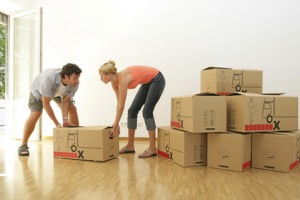 Young Couple Moving Boxes of Belongings Into New Home